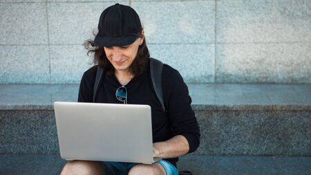 Freelancer working in the open air, concept, young man with long hair sits on the granite steps in the shade, with a laptop. Summer windy day. Copy space. Front view 版權商用圖片 - 129310467