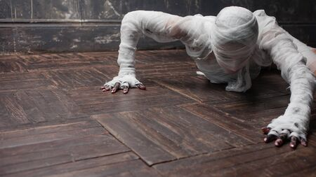 Scary mummy creeps on you. The girl with the bandage Crawling on the floor. Halloween costume Banco de Imagens