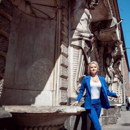 Walk through the historic center. Beautiful girl, blonde with a ponytail and curls in a blue pantsuit, jacket against a gray historical buildings with decorations. Фото со стока
