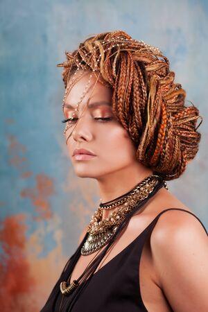 Saveur du sud. Portrait d'une femme bronzée luxueuse, pensive, élégante, avec une coiffure exotique et de gros bijoux, collier, boucles d'oreilles, sur fond de mur texturé multicolore.