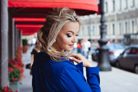 In search of coffee. Portrait of a beautiful young woman, a blonde on the background of red window marquises of restaurants in the center of a large, vibrant city.
