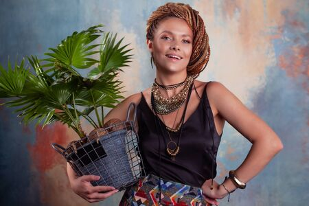 Southern flavor. A young tanned woman with afro braids smiles holding a big pot with a tropical plant. On her neck she has large jewels in ethnic style. Фото со стока