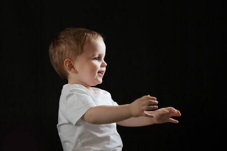 Happy cheerful baby on black background. Little boy looks and rejoices to the right side, free space for text or design