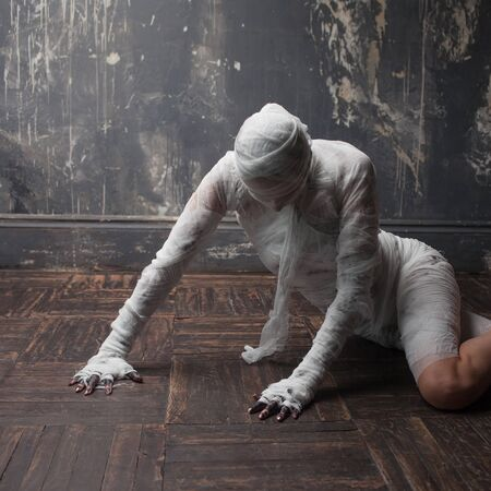 Scary mummy creeps on you. The girl with the bandage Crawling on the floor. Halloween costume Фото со стока