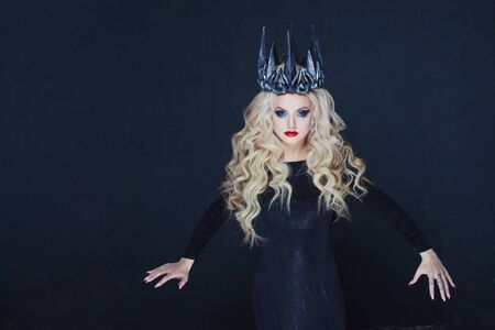 Chic Gothic Queen from a dark fairy tale. Young blonde woman in black with steel crown on her head. Mystical image