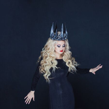 Portrait of a Gothic Queen. Beautiful young blonde woman in metal crown and black cloak. Mystical image