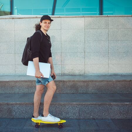 A young man with a laptop under his arm stands on the background of a gray wall, putting one foot on a yellow skate. Copy space Фото со стока