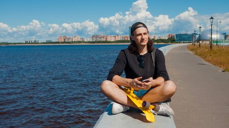 A young man in a baseball cap with a smartphone and a yellow skateboard sits on the parapet of the city embankment on a sunny summer day against the background of the sea and clouds in the sky. 版權商用圖片 - 129383802
