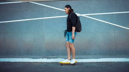 A young man in a baseball cap, with a backpack, and in denim shorts with a laptop under his arm, drives past a gray granite wall with white stripes. Copy space. 版權商用圖片 - 129383750
