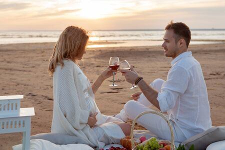 Romantic sunset. A man and a woman had a picnic on the sand, with a blanket, pillows, a lantern, fruit, and sweet pastries. They drink from glasses against the setting sun. Clink glasses. Zdjęcie Seryjne