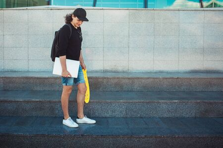A young man with a laptop in one hand and a yellow skate in the other is standing against a gray wall. Copy space 版權商用圖片