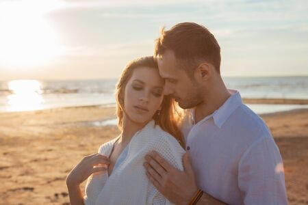 Love, romance, walk. Portrait of a beautiful couple in white kissing on the background of the sunset sea, sandy beach and sky with clouds. Side view. Reklamní fotografie - 130617733
