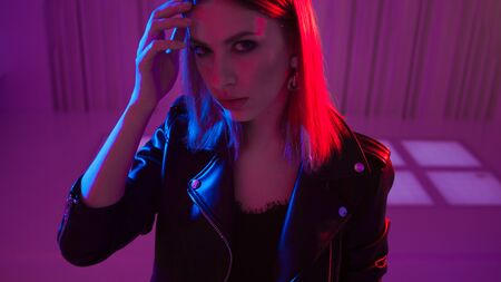 Beautiful girl dancing in retro wave on the neon light. Fashion portrait of trendy young woman in leather jacket, blue and purple light on her face
