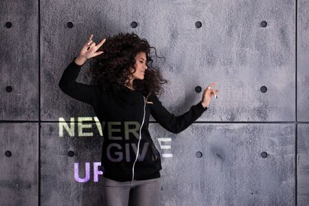 Cheer up! Cheerful young curly woman dancing on a concrete wall background. Multi-colored light inscription, the projection says: Never give up. Copyspace.