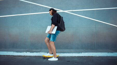 A young man in a baseball cap, with a backpack, and in denim shorts with a laptop under his arm, drives past a gray granite wall with white stripes. Copy space.