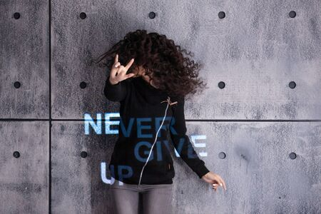 Cheer up. Cheerful young curly woman dancing on a concrete wall background. Multi-colored light inscription, the projection says: Never give up. Copyspace.