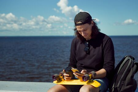 A young man in a baseball cap with a smartphone and a yellow skateboard sits on the parapet of the city embankment on a sunny summer day against the background of the sea and clouds in the sky. 版權商用圖片