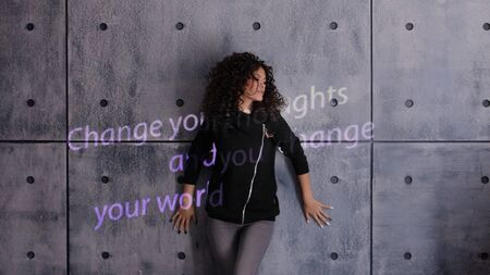 Curly young woman actively posing on a concrete wall background. A colored light sign is projected onto the wall that reads: Change your thoughts and you change your world. Copyspace.