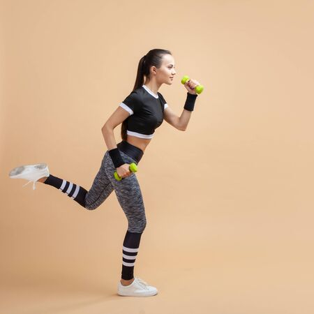 Young attractive brunette girl runs with wireless headphones and green dumbbells, on a peach background, cardio. Copy space