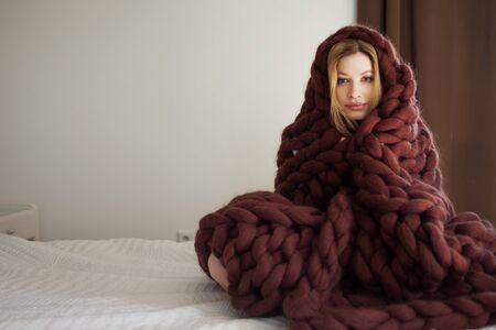 Cute young blonde at home in the bedroom, sitting on the bed wrapped in a big brown blanket. A young woman at home basking in a cozy blanket.