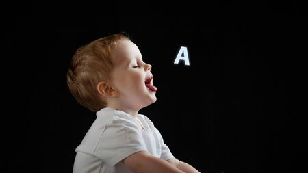Baby says, the concept of problems with dyslexia and dysgraphia. A child learns to speak, a boy on a black background, a letter A on the right
