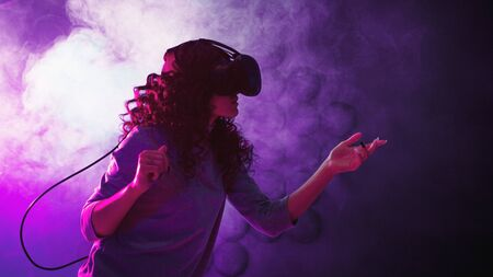 Virtual reality game. A girl in a virtual reality helmet plays a game or explores the environment. Portrait in neon light, retrowave style Stock Photo