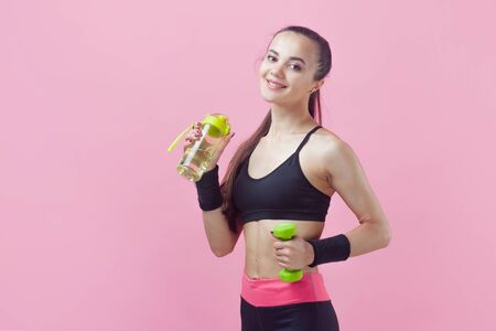 Portrait of an attractive athletic brunette girl, cute, with a tight-fitting athletic uniform, with a green dumbbell in one hand and a bottle for sports nutrition in the other on a pink. Copy space Reklamní fotografie