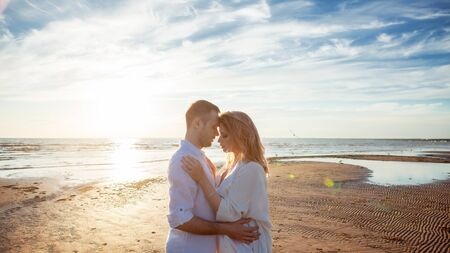 Love, romance, walk. Portrait of a beautiful couple in white kissing on the background of the sunset sea, sandy beach and sky with clouds. Side view.