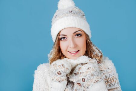 Happy girl laughing in winter clothes. Young woman in knitted sweater hat and mittens