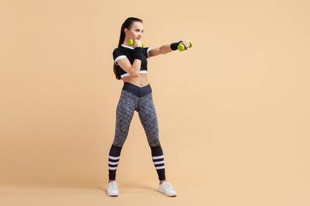 A young girl, a brunette with a ponytail, works out punches using extra weights, a full-length photo, against a peach background. Copy space