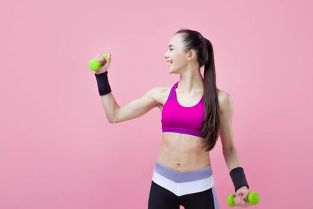 A young athletic attractive brunette girl with a ponytail in a bright top shows off her biceps, holding a green dumbell in her hand on a pink background. Girl power. Copy space Reklamní fotografie