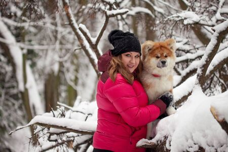 Portrait of a cute fluffy puppy. Akita inu with long hair. Mistress on the walk hugs the dog Imagens