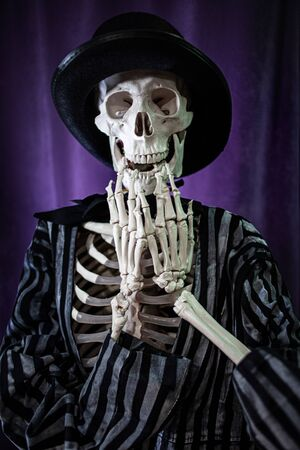 surprised skeleton in a striped suit and top hat. Halloween Is Coming