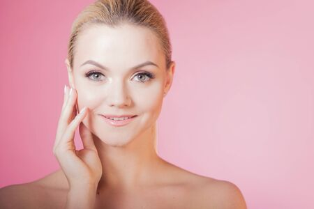 Face care and skin care, health and beauty concept, copy space. Portrait of young beautiful woman, healthy skin and minimum makeup, naturalness and beauty. Charming blonde girl on pink background