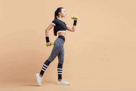 A young girl, brunette with a ponytail and in long gray leggings, jumps up and down with green dumbbells in her hands, raising one knee high. Copy space Banque d'images