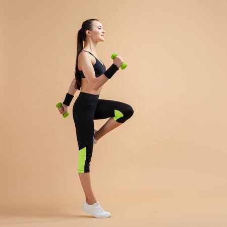 A young brunette girl raises her knees high, using extra weights, a full-length photo, against a peach background. Copy space