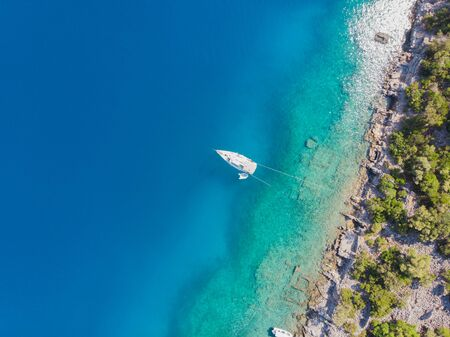 Sailing yacht moored to the shore, a delightful seascape drone photo. Clear blue sea
