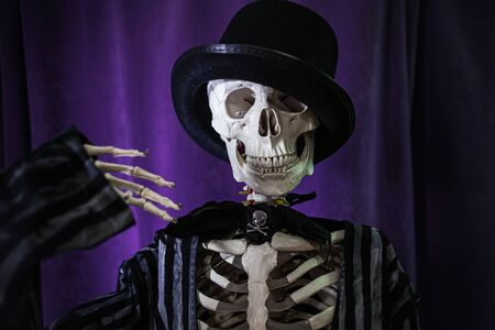 Funny human skeleton in a jacket and bowler hat. Halloween, skeleton waving cheerfully