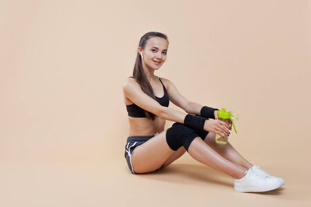 Young athletic attractive girl brunette with a ponytail in a black top and black knee-pads sits on the floor, rests after a workout, prepares for new exercises, takes a break