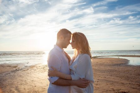 Love, romance, walk. Portrait of a beautiful couple in white kissing on the background of the sunset sea, sandy beach and sky with clouds. Side view. Reklamní fotografie - 130618338