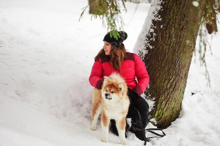 Portrait with a cute fluffy puppy. Winter walk with a dog. young woman walks with the puppy, snowy winter Imagens
