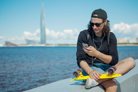 A young man sitting on the embankment with a yellow skateboard on his lap makes a photo of the cityscape against the sky, clouds, sea, and modern urban architecture. Copy space