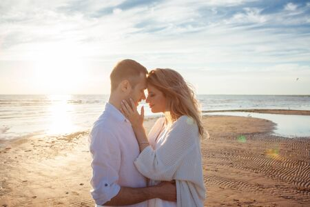 Love, romance, walk. Portrait of a beautiful couple in white kissing on the background of the sunset sea, sandy beach and sky with clouds. Side view. Reklamní fotografie - 130612784