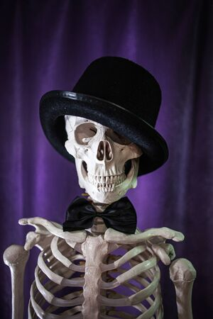 Funny human skeleton in a bowler hat and bow tie. Skeleton invites to Halloween. Banque d'images
