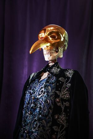 Gentleman skeleton in doublet and gold plague doctor mask, waiting for Halloween