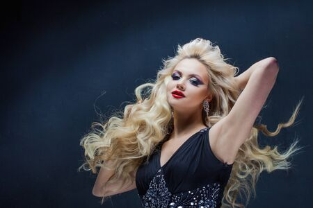 Portrait of a young luxurious blonde with long curls. bright makeup for party, dark background Фото со стока
