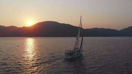 Yachting, a beautiful white yacht is sailing off the coast. Pink sunset the sun sets behind the mountains