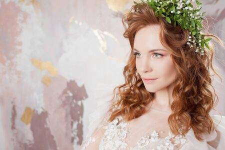 Portrait of a young beautiful woman in wedding dress with wreath of fresh flowers. red-haired bride