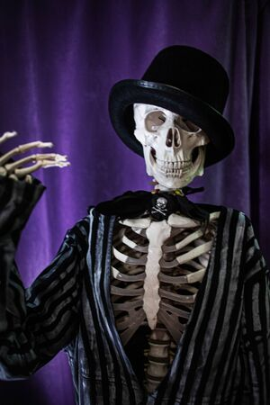 Funny human skeleton in a jacket and bowler hat. Halloween, skeleton waving cheerfully Stockfoto