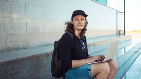 A young brunette man with long hair is sitting on the granite steps with a laptop spread out on his lap and looking thoughtfully into the distance. Summer windy day. Copy space. Side view Reklamní fotografie - 130777320